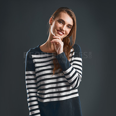 Buy stock photo Studio portrait of a cheerful young woman holding her chin while standing against a dark background