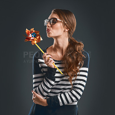 Buy stock photo Studio shot of an attractive and playful young woman holding a pinwheel and blowing it while standing against a dark background