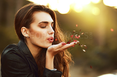 Buy stock photo Shot of an attractive young woman blowing confetti from her hand outdoors