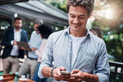 Buy stock photo Shot of a businessman using a cellphone outside with his colleagues in the background