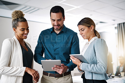 Buy stock photo Shot of a group of businesspeople working on a digital tablet in an office