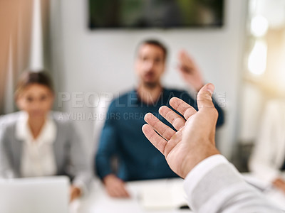 Buy stock photo Closeup shot of an unrecognizable businessman gesturing towards a colleague during a meeting in an office