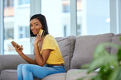 Buy stock photo Shot of a teenage girl using a cellphone and credit card at home