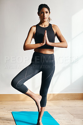 Buy stock photo Shot of an attractive young woman practising yoga at home