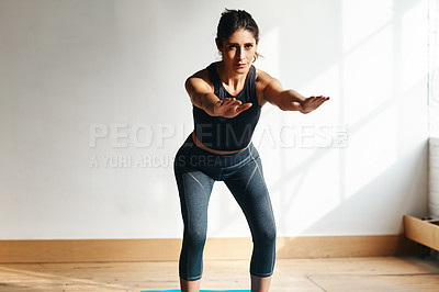 Buy stock photo Shot of an attractive young woman exercising at home