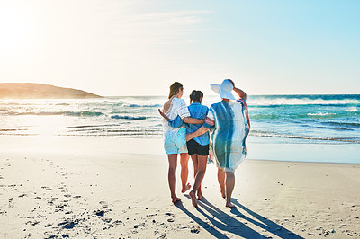 Buy stock photo Rearview shot of a senior woman spending the day at the beach with her daughter and granddaughter