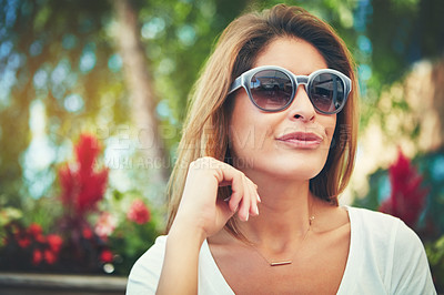 Buy stock photo Shot of a confident young woman wearing sunglasses while sitting at a restaurant outside during the day