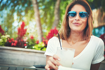 Buy stock photo Portrait of a cheerful young woman wearing sunglasses and enjoying a cold beverage while being seated at a restaurant outside during the day