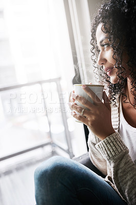 Buy stock photo Shot of a cheerful young woman enjoying a cup of coffee while being seated on a chair at home during the day