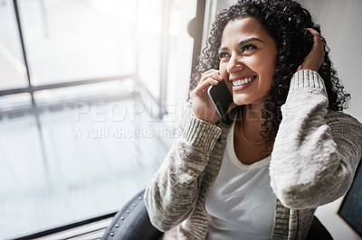 Buy stock photo Shot of a cheerful young woman relaxing while talking on her cellphone at home during the day