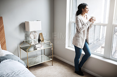 Buy stock photo Shot of a cheerful young woman drinking coffee while looking through a window inside at home during the day