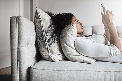 Buy stock photo Shot of a carefree young woman relaxing on a couch while texting on her cellphone at home during the day