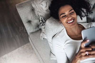 Buy stock photo Shot of a cheerful young woman relaxing on a couch while texting on her cellphone at home during the day