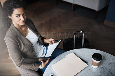 Buy stock photo Shot of a young businesswoman reading through a business folder while waiting for her flight in an airport lounge