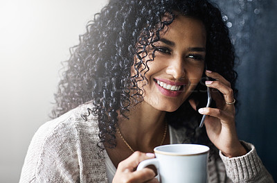 Buy stock photo Shot of a cheerful young woman relaxing and drinking coffee while talking on her cellphone at home during the day