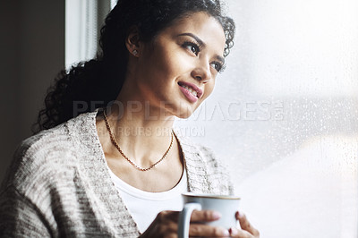 Buy stock photo Shot of an attractive young woman relaxing at home with a cup of coffee
