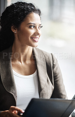 Buy stock photo Shot of a young businesswoman reading through a business folder in an office