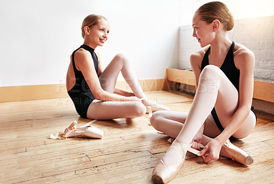 Buy stock photo Shot of two young girls putting on their ballet slippers in a dance studio