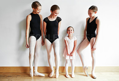 Buy stock photo Shot of a group of young ballerinas teaching a little girl ballet in a dance studio