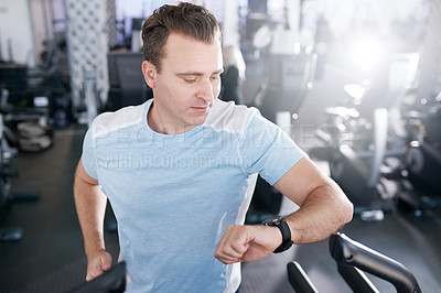 Buy stock photo Shot of a mature man looking at his watch while exercising on a treadmill in a gym
