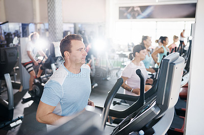 Buy stock photo Shot of a mature man exercising on a treadmill in a gym