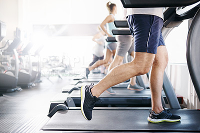 Buy stock photo Cropped shot of a group of people exercising on treadmills in a gym