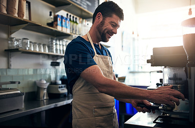 Buy stock photo Shot of a barista operating a coffee machine in a cafe