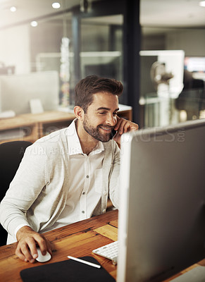 Buy stock photo Shot of a handsome young businessman talking on a cellphone while working late in an office
