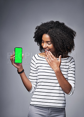 Buy stock photo Studio shot of a young woman showing a smartphone with a green screen against a gray background