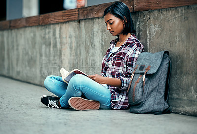 Buy stock photo Shot of a young female student reading a book outside on campus
