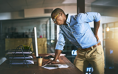 Buy stock photo Shot of a young businessman suffering from backache while working at his desk during a late night at work