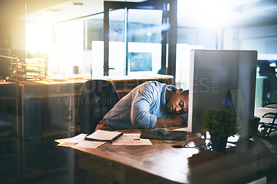 Buy stock photo Shot of an exhausted young businessman sleeping at his desk during a late night at work