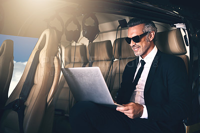 Buy stock photo Shot of a mature businessman using a laptop while traveling in a helicopter