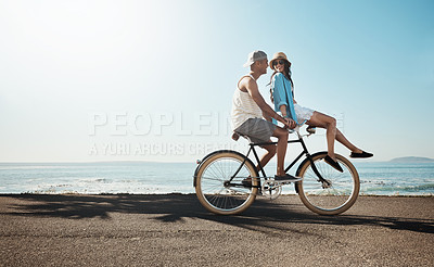 Buy stock photo Shot of a young couple riding a bicycle together on the promenade