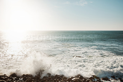 Buy stock photo Shot of water crashing against some boulders at the beach