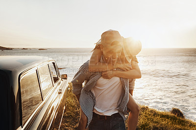 Buy stock photo Shot of a happy young couple enjoying a piggyback ride on a road trip