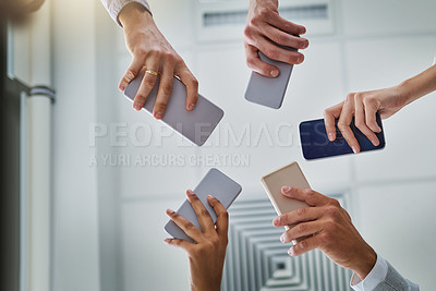 Buy stock photo Low angle shot of an unrecognizable group of businesspeople using their cellphones in synchronicity