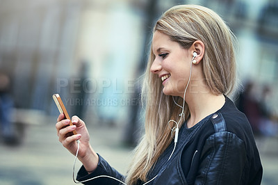 Buy stock photo Shot of an attractive woman using a mobile phone and earphones in the city