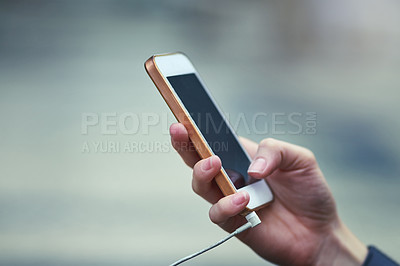 Buy stock photo Cropped shot of a woman using a mobile phone outdoors