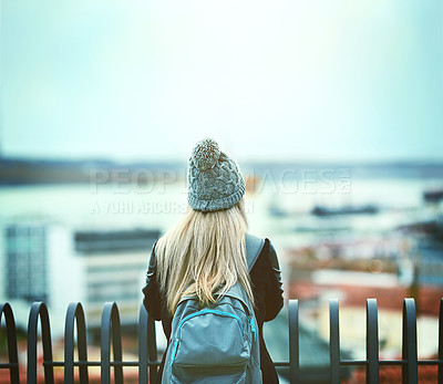 Buy stock photo Rearview shot of a young woman looking at the city view from a bridge