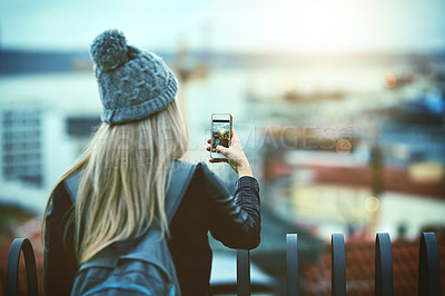 Buy stock photo Rearview shot of a young woman using a cellphone to take pictures of a city view from a bridge