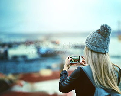 Buy stock photo Rearview shot of a young woman using a cellphone to take pictures of a city view