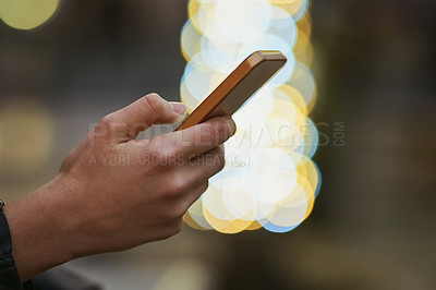 Buy stock photo Cropped shot of a woman using a mobile phone in the city at night