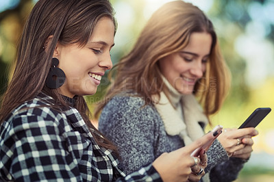 Buy stock photo Cropped shot of two attractive young women using their cellphones while sitting in the park