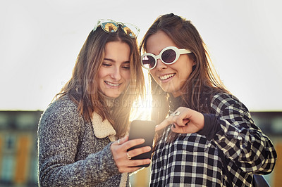 Buy stock photo Cropped shot of two attractive young women using a cellphone while out in the city