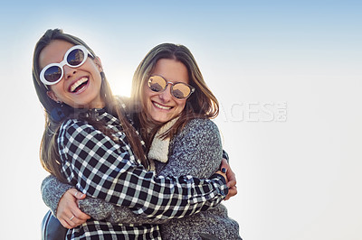 Buy stock photo Cropped portrait of two attractive young women embracing while standing outdoors