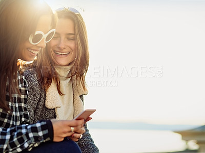 Buy stock photo Cropped shot of two attractive young women using a cellphone while out by the ocean
