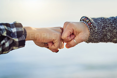 Buy stock photo Cropped shot of two unrecognizable women fist bumping outdoors