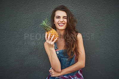 Buy stock photo Portrait of a cheerful young woman holding a pineapple while winking and standing against a grey background
