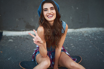Buy stock photo Portrait of a cheerful young woman seated on a skateboard while showing the peace sign outside during the day